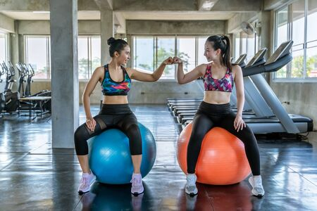 two beautiful Asian women are fisting their confidence in exercising in the gym.the concept of exercise, lose weight, strengthen muscles.