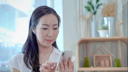 Asian middle-aged women are playing mobile phones Stok Fotoğraf