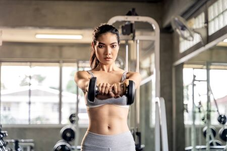 Asian beautiful woman is lifting double in the gym, She smile happily in exercise because it makes her shapely, the concept of exercise, lose weight, strengthen muscles. 版權商用圖片