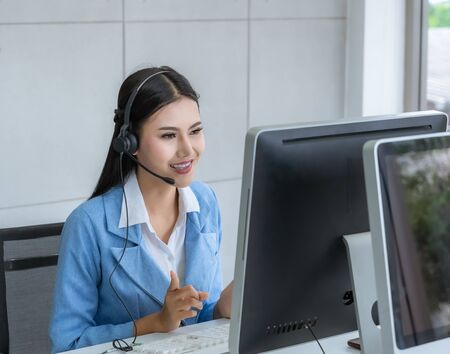 Call Center Asian women are providing business information services in a smile. Reklamní fotografie - 135494332