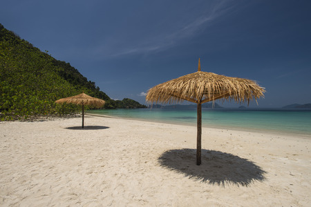 Straw parasol with cloudscape and calm sea water on sand beach