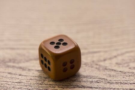 Brown dices on wooden background. Concept of luck, chance and leisure fun. Sensitive Focus  this dice by handmade
