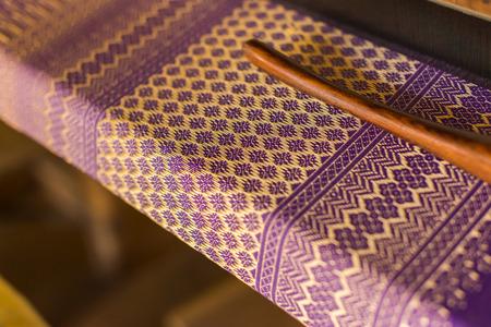 trabajo manual: Hermoso diseño tailandés de tela tradicional, hilo púrpura y dorado, enfoque sensible