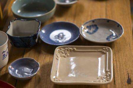 homeware: Handmade ceramic dishes on an old vintage table, Sensitive Focus