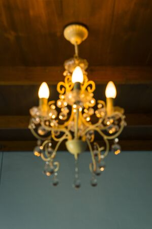 image of blur chandelier with bokeh in orange light tone for background usage