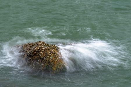 Sea waves breaking on a rocks. Deep blue sea waves hit cliff, hit rocks cliff. Mighty sea waves breaking on a cliff, splashing over rocks. Strong ocean waves hitting rocks.