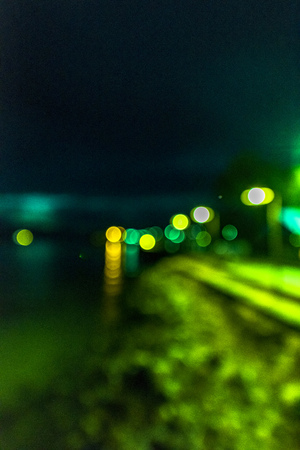 Night twilight blurred light gold bokeh reflecting on the sea surface water abstract background.