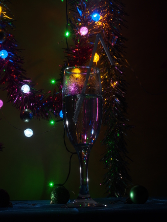 A champagne glass stands on the table. The photo on the background of Christmas light. Still life. Stock Photo