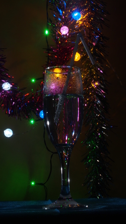 A champagne glass stands on the table. The photo on the background of Christmas light. Still life. Фото со стока