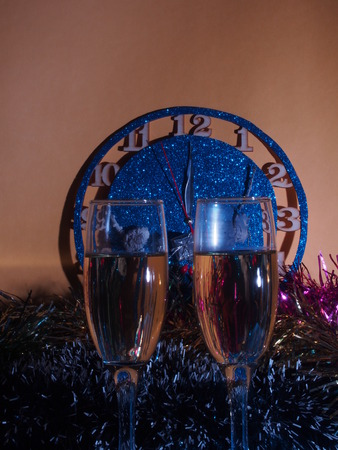 Glasses with champagne on the background of the clock. The clock approaching twelve oclock. Christmas still life.
