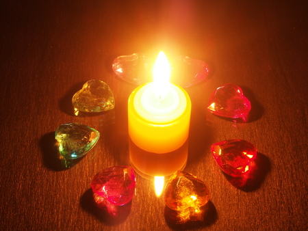 A burning candle and a transparent decorative colored stones. The stones in the form of hearts and roses. Still life.