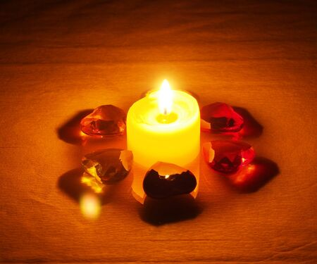 Burning candle lying around it is transparent with colored stones in the form of hearts. Still life