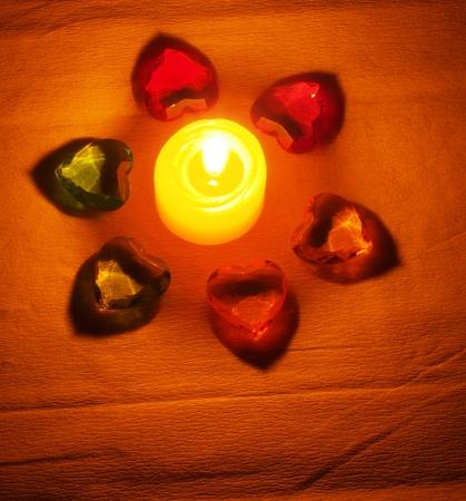 그 주위에 누워있는 불타는 촛불은 마음의 형태로 색깔이있는 돌로 투명하다. 정물 스톡 콘텐츠