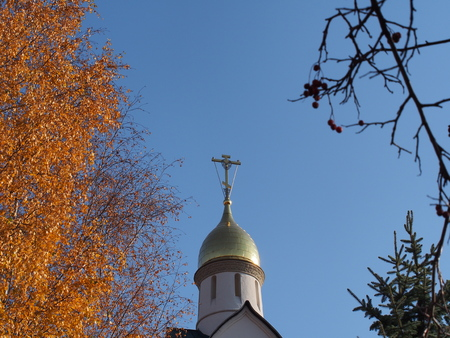Orthodox cross framed by yellow autumn leaves of trees. Dome of the Orthodox Christian Church.