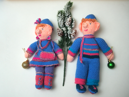 Two handmade dolls with Christmas decorations. Knitted dolls. Subject photography.