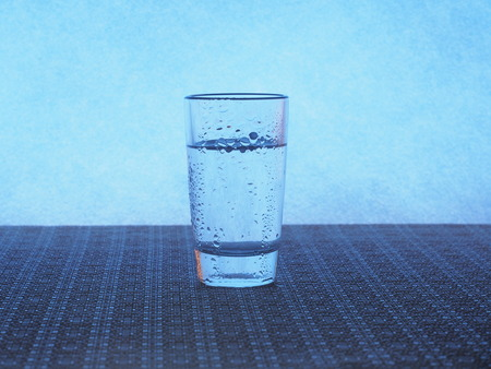 A glass of vodka is on the table. The glass is covered with water droplets. Still-life.