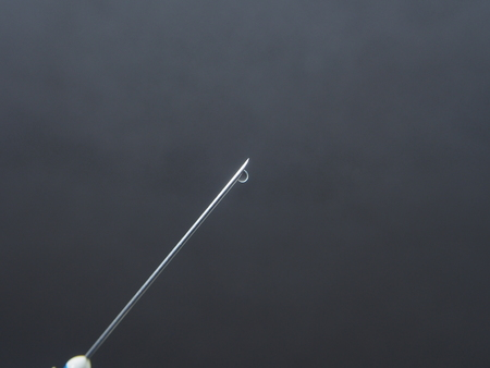 A drop of medicine on the end of a medical syringe needle. Photo on a black background.
