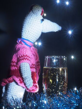 Rat doll with a glass of sparkling wine on the background of Christmas lights garland. The symbol of the new year according to the Eastern tradition. Still-life. 免版税图像