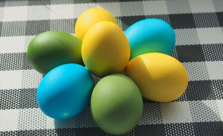 Colorful Easter eggs lie on a checkered tablecloth. Yellow, blue, green eggs. Still-life.