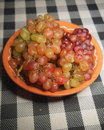 Clusters of sultana grapes lie in a brown clay plate. Still-life