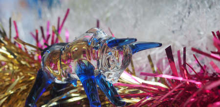 Glass figure of a bull on the background of colorful Christmas tinsel. Symbol of the year 2021. Close-up. 免版税图像