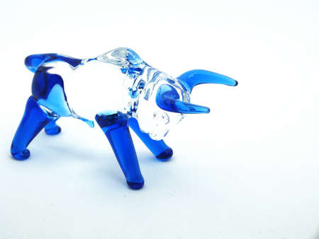 Glass figure of a bull with blue horns and legs on a white background. Close-up 免版税图像