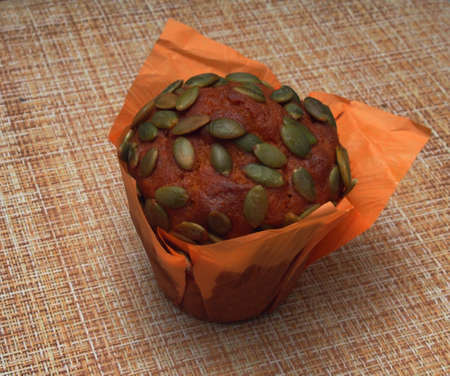 On the table, covered with a brown tablecloth, is a cupcake with pumpkin seeds. Still-life
