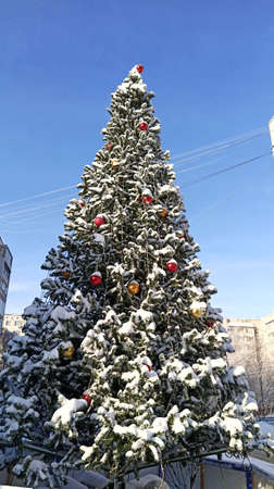 Artificial Christmas tree decorated with Christmas toys and covered with snow. Christmas 免版税图像