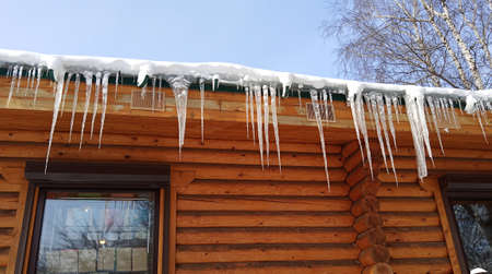 Long icicles hang from the roof of a wooden log house. Cold 免版税图像