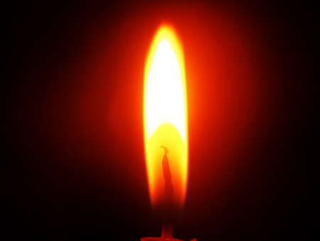 The flame of a burning candle on a black background. Close-up. 免版税图像