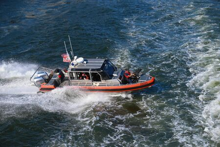 A Coast Guard vessel on patrol following the Staten Island Ferry in New York City harbor.