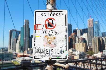 A sign on the Brooklyn Bridge covered in stickers and graffitti. Фото со стока
