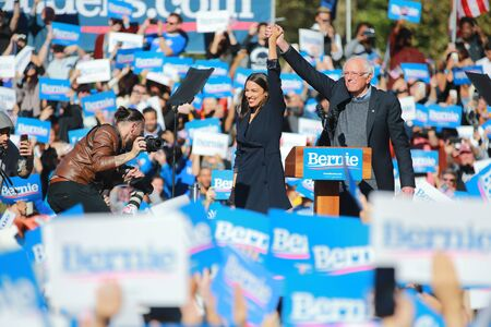 U.S. Representative Alexandria Ocasio-Cortez, Democrat of New York on stage with Vermont senator and Democratic presidential candidate Bernie Sanders at the Bernie's Back Rally in Long Island City, N.Y. on Saturday, Oct. 19, 2019. (Photo: Gordon Donovan) Фото со стока - 133263796