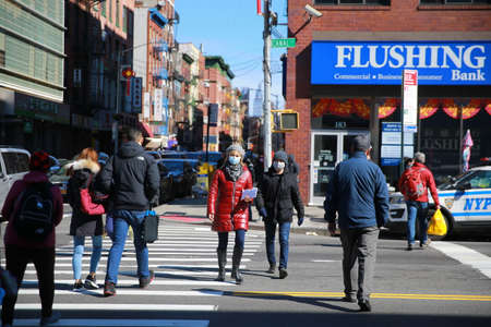 People walk the quiet streets of Chinatown on Sunday, March 15, 2020, in New York.