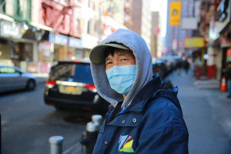 People wear face masks as they walk along the quiet streets  of Chinatown in New York on Sunday, March 15, 2020. Senior public health officials called on the nation to act with more urgency to safeguard their health as the coronavirus outbreak continued t Sajtókép
