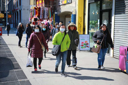People walk the quiet streets of Chinatown on Sunday, March 15, 2020, in New York. (Photo: Gordon Donovan)