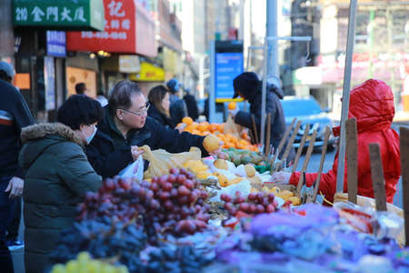 People wear face masks as they buy fruit along the quiet streets of Chinatown in New York on Sunday, March 15, 2020. Senior public health officials called on the nation to act with more urgency to safeguard their health as the coronavirus outbreak continu