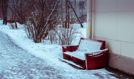aloneness: red old couch standing in the street covered with snow