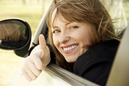 throw up: Happy smiling girl in the car looking throw window and showing thumb up Stock Photo