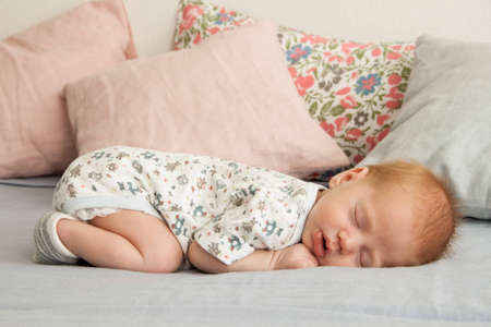 Cute newborn baby boy sleeping on a blanket and pillows photo
