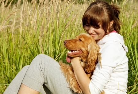 Young smiling girl embracing her dog on the green grass photo