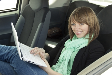 comp: Young woman enjoy by using laptop sitting in the car