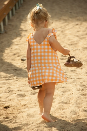 Back view of cute barefoot baby girl walking on beach with sandals in hands photo
