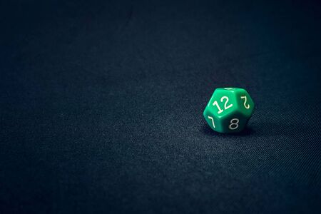 12 sided green die for a game on a background Banco de Imagens