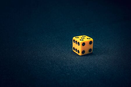 6 sided yellow die for a game on background