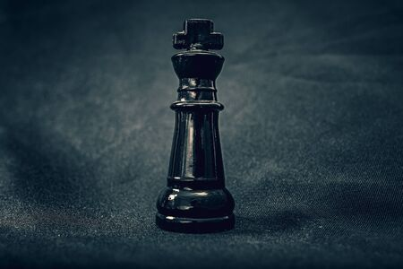 Black glass King chess piece on dramatic background