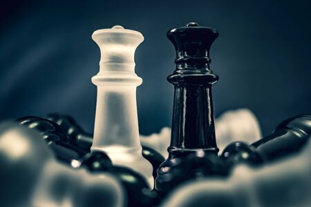 black and white glass queens dominating chess board