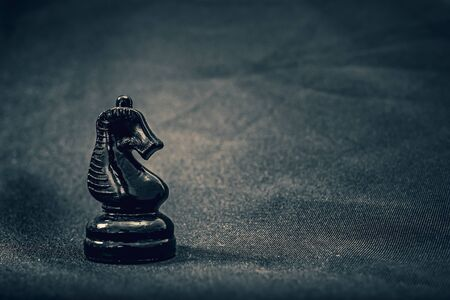 black glass knight chess piece on background