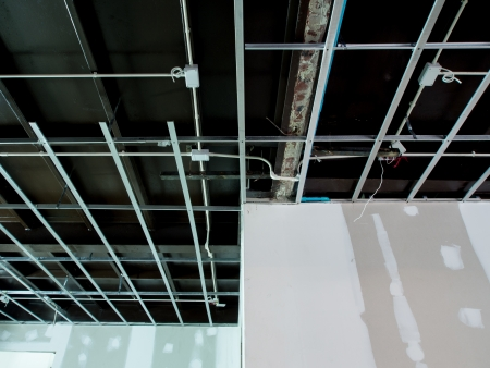 Interior remodeling work on an existing commercial building - ceiling is being prepared for electricity system and wall are prepared for painting