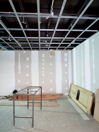 ceiling construction: Interior remodeling work on an existing commercial building - ceiling is being prepared for electricity system and wall are prepared for painting